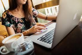 Femme avec un café sur son ordi